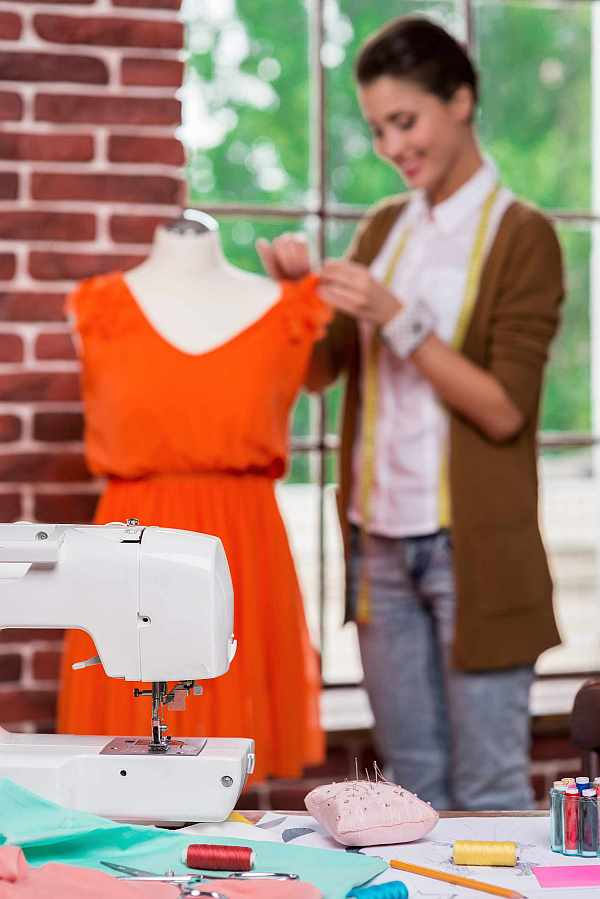 Beautiful young fashion designer adjusting dress on the mannequin and smiling with sewing machine on the foreground